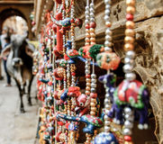 Cows of Jaisalmer, Rajasthan, India. Vaus of decorative wooden elephants and birds in different colors and a cow out of focus Royalty Free Stock Photo