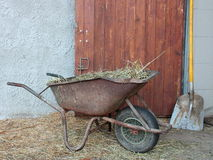 Cowshed entrance with wheelbarrow and shovel. Cowshed entrance with brown wooden door wheelbarrow and shovel Stock Photos