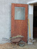 Cowshed entrance with wheelbarrow and shovel. Cowshed entrance with brown wooden door wheelbarrow and shovel Stock Photography