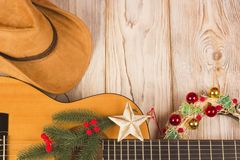 Cowvoy christmas background with guitar and cowboy western hat. Cowvoy christmas wood background with guitar and cowboy western hat royalty free stock photos