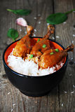 Coxas de frango alaranjadas com arroz na bacia Foto de Stock