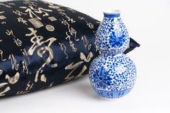Coxim com os caráteres chineses que escrevem e o vaso cerâmico azul fotos de stock royalty free