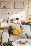 Coxim feito a mão amarelo do nó colocado no sofá cinzento no livin branco imagem de stock