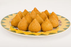 Coxinha de Galinha. Brazilian breaded and deep fried snacks filled with shredded chicken on a colourful plate on a white background Stock Images