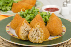 Coxinha de Galinha. Brazilian breaded and deep fried snack filled with shredded chicken served with chili dip. Rissoles on the background Royalty Free Stock Photo
