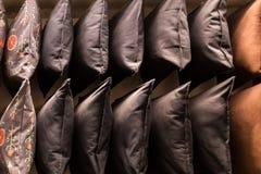 Coxins coloridos confortáveis da tela em prateleiras de loja muitos descansos na prateleira na loja imagens de stock
