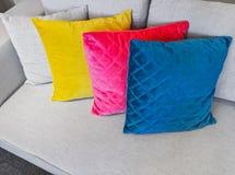 Coxins coloridos que decoram um sofá cinzento Foto de Stock