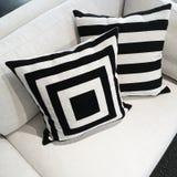 Coxins preto e branco em um sofá fotografia de stock