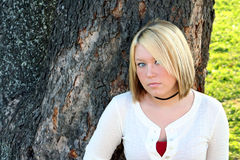Coy Blond. Serious young blond woman with a coy expression, standing in front of a large tree outdoors stock photos