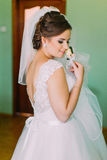 Coy bride in white dress posing, holding cute little boutenniere and looking over her shoulder stock photo