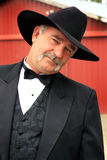 Coy Formal Cowboy. A coy middle aged American rancher with a full mustache wearing formal western wear, with barn in background. shallow depth of field Stock Photo