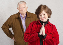 Coy Woman with Grumpy Man. Coy pretty older women in front of grumpy man Stock Images