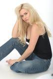 Coy Young Blonde Woman Sitting lindo atractivo en el piso que parece relajado Fotos de archivo libres de regalías