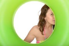 Coy Young Woman Looking Through fresco atractivo un anillo de goma verde Fotos de archivo