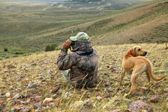 Coyote hunter and dog scanning for prey from hill. A camouflaged coyote hunter with a tracking dog, scans an arid landscape for prey with a pair of binoculars Stock Photos