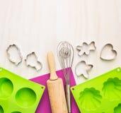 Coza ferramentas com molde do bolo e no fundo de madeira branco Fotografia de Stock Royalty Free