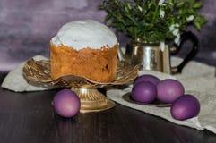 Cozeu recentemente o bolo da Páscoa na mesa de cozinha coberta com a crosta de gelo e que decora a cobertura com ovos roxos Conce fotografia de stock