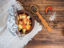 Cozido em uma bacia cerâmica de batatas com carne da galinha Ainda vida no estilo country em um fundo da madeira velha e áspero Fotos de Stock