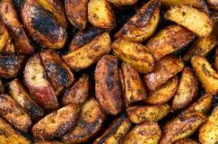 Cozido na grade, em batatas Roasted com alecrins e em especiarias pronto para comer Fundo, textura Foto de Stock