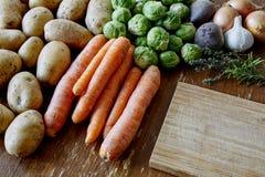 Cozimento com batatas e brotos das cenouras foto de stock