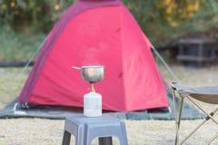 Cozimento com o fogão de gás no local de acampamento Foco seletivo no queimador, no potenciômetro e no fumo de gás da água a ferv Foto de Stock
