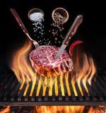Cozimento cru do bife Retrato conceptual Bife com especiarias e cutelaria sob a grelha de queimadura da grade imagem de stock