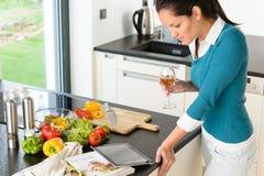 Cozimento da cozinha da receita da tabuleta da leitura da jovem mulher Fotos de Stock Royalty Free