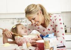 Cozimento da matriz e da filha na cozinha Fotografia de Stock Royalty Free