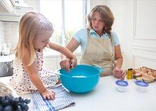 Cozimento da menina com sua avó em casa Imagem de Stock