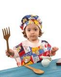 Cozimento da menina vestido como um cozinheiro chefe Imagem de Stock Royalty Free