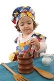 Cozimento da menina vestido como um cozinheiro chefe Fotografia de Stock