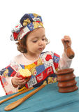 Cozimento da menina vestido como um cozinheiro chefe Fotos de Stock