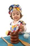Cozimento da menina vestido como um cozinheiro chefe Imagens de Stock Royalty Free