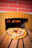 Cozimento da pizza com fogo de madeira Imagem de Stock