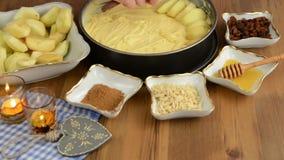 Cozimento da torta de Apple Passas polvilhadas na torta de maçã crua A adição, lá é ingredientes tais como o mel, canela, açúcar, video estoque
