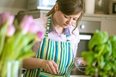 Cozimento de encantamento da mulher nos muffin de blueberry da cozinha em casa fotografia de stock royalty free