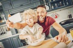 Cozimento de fotografia alegre jovial do menino e do homem foto de stock
