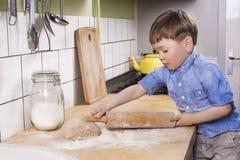 Cozimento do rapaz pequeno na cozinha Foto de Stock