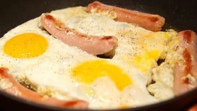 Cozimento dos ovos mexidos Cozinheiro chefe que cozinha a omeleta Fritura dos ovos e das salsichas filme