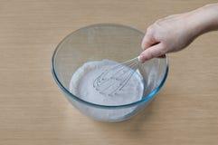 Cozimento e mistura em uma bacia para preparar um creme fotografia de stock
