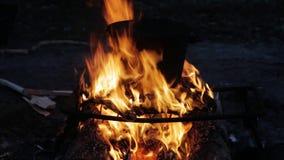 Cozimento em uma cubeta na fogueira na noite filme