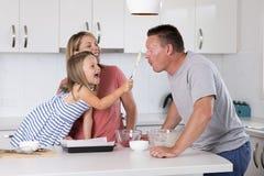 Cozimento feliz novo dos pares junto com a cozinha bonita nova pequena da filha em casa que tem o divertimento que joga com creme imagem de stock royalty free