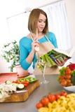 Cozimento - livro de receitas da leitura da mulher na cozinha Imagem de Stock