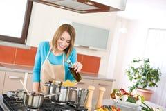 Cozimento - mulher nova com espaguete no fogão foto de stock
