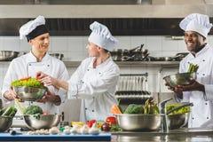 cozimento multicultural alegre dos cozinheiros chefe fotografia de stock royalty free