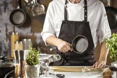 Cozimento, profissão e conceito dos povos - cozinheiro masculino do cozinheiro chefe que faz o alimento na cozinha do restaurante fotografia de stock