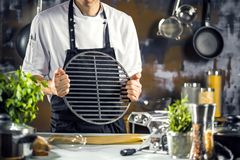 Cozimento, profissão e conceito dos povos - cozinheiro masculino do cozinheiro chefe que faz o alimento na cozinha do restaurante fotografia de stock royalty free