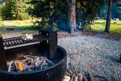 Cozimento sobre a grade aberta ao acampar na região selvagem imagem de stock