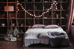 Coziness, comfort, interior and holidays concept - cozy bedroom with bed and garland lights at home. A rack with books. Behind the bed. Candles, a lamp and a stock photography