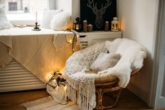 Coziness, comfort, interior and holidays concept - cozy bedroom with chair and christmas garland lights at home. Candle stock photography